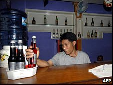 An Indonesian bar tender reaches to serve a drink.