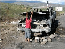 boy playing with burnt out car after the clashes