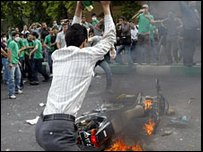 Protester throws stone at burning police motorbike (13/06)