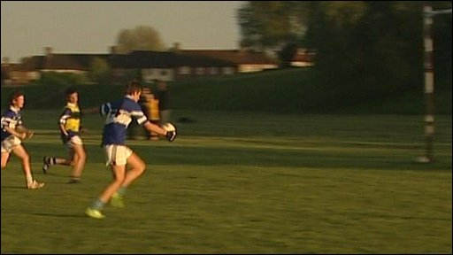 gaelic footballer runs with ball