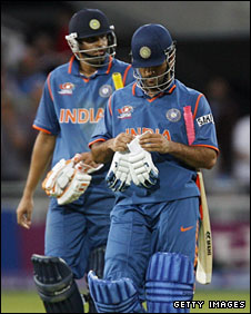 Captain Mahendra Dhoni (right) and Yusuf Pathan walk off after India's defeat