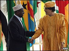 Libyan leader Muammar Gaddafi (R) welcomes Somalia President Sharif Sheikh Ahmed (L) to the African Union Summit