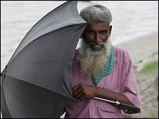 Man sheltering behind umbrella (Image: BBC)
