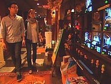 A couple walk through the lobby of a love hotel, looking at a bank of screens