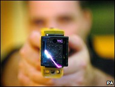 A police officer points a Taser gun at the camera, file photo from June 2009