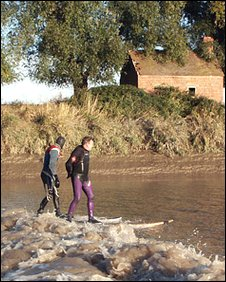 Two surfers ride the Severn Bore
