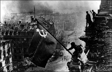 Russian soldier flies the Red Flag on top of the ruins of the Reichstag in Berlin (1945)