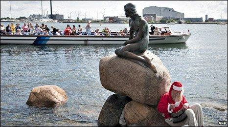A santa rests at The Little Mermaid sculpture in Copenhagen Harbour on the second day of the World Santa Claus Congress 2009