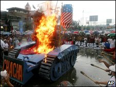 Protesters burn an effigy of Philippine President Gloria Macapagal Arroyo inside a mock tank near the Philippine Congress on 27 July 2009