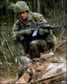 A Colombian soldier stares at the body of a Farc rebel during operations on 25 July