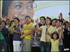 People, many dressed in symbolic yellow, hold candles in front of a huge poster of Mrs Aquino