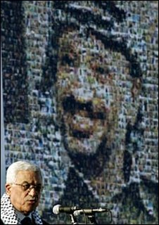 Mahmoud Abbas speaks in front of a poster showing Yasser Arafat