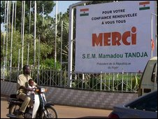 "A man rides by a street billboard featuring a message from Niger""s President Mamadou Tandja reading "" Thank you for your trust"""