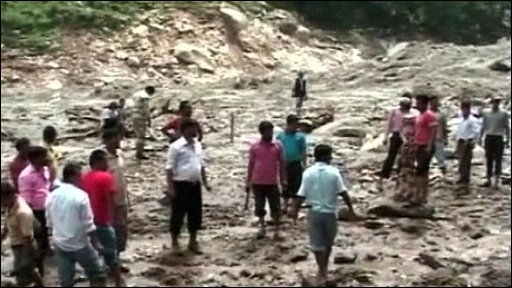 People walking over thick mud where an Indian village was buried by a landslide