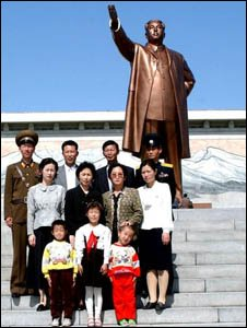 A North Korean family poses in front of Kim Il-sung's statue