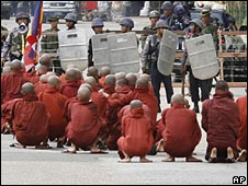 Monks squat in front of troops in Rangoon on 26 September 2007
