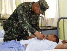 Maj Gen Benjamin Dolorfino pins a medal to a wounded soldier at a military hospital in Zamboanga City - 13 August 2009