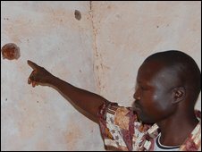 Luka Kitimbi shows bullet holes in his wall
