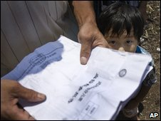 A child next to a villager holding blood test results in Wenping township in Hunan province, Aug 22