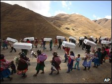 Relatives carry coffins containing the remains of victims of the 1984 massacre during a funeral ceremony in Putis, Peru, 29 August 2009