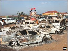 Burnt-out cars litter the street around the razed Nateete police station in Kampala, Uganda on Saturday