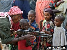"A government soldier on patrol in the streets of Somalia""s war-torn capital demonstrates to Somali children how to use a Kalashnikov rifle"