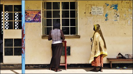 Two women outside a health centre in Ssekiwumna