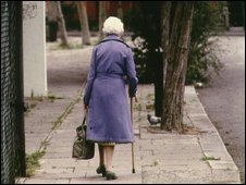 An elderly woman walks down a street