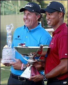 Phil Mickelson (left) holds the Tour Championship trophy while Tiger Woods holds the FedEx Cup