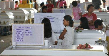 Families wait by coffins in Quezon City, 29/09