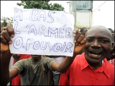 "A Guinean holds on September 28, 2009 a sign, reading: ""Down With the Army In Power"""