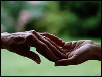 Young person's hand holding older person's hand