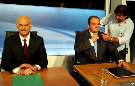 A Greek state television technician prepares Prime Minister Costas Karamanlis, right, for a televised debate against Socialist leader George Papandreou in Athens, Greece, 21 September 2009.