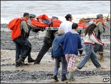 Rescuers carry a woman on a stretcher near Messina, southern Italy, 2 October 2009