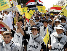 Palestinian and Syrian children hold Syrian and yellow Hezbollah flags during a rally marking Al-Quds Day near Damascus (18 August 2009)