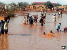 Residents of the city of Agadez, nothern Niger, walk in a flooded street