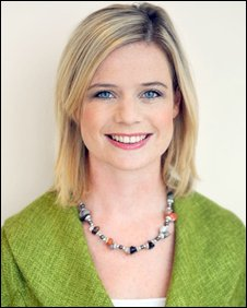 Head and shoulders shot of Sarah Keith-Lucas wearing a bright-green jacket and multi-coloured beaded necklace.