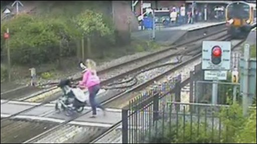 A woman running across a railway line with a pram in front of an approaching train