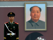 Paramilitary policemen stands guard near portrait of late Chinese leader Mao Tse-Tung