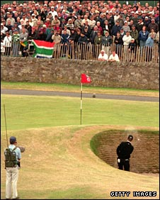 A player hits a shot out of the Road Bunker on to the 17th green