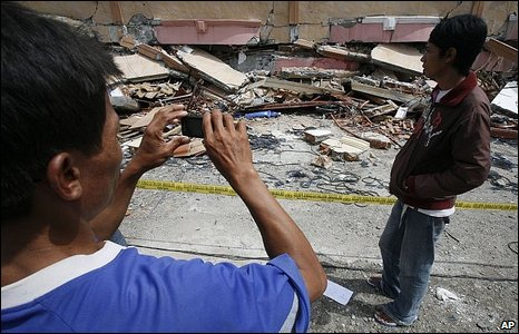A man takes a picture of a ruined building with a mobile phone