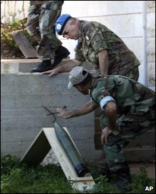 Unifil commander Maj Gen Claudio Graziano, background, and a Lebanese soldier check a rocket that was set to be fired into Israel