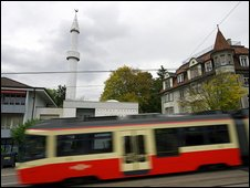 A tram passes by the Mahmud Mosque and its minaret, Zurich (26 Oct 2009)