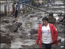 People walk in street damaged by boulders and mud in Verapaz, El Salvador