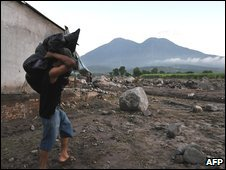 A man carries his belongings after a landslide in El Salvador