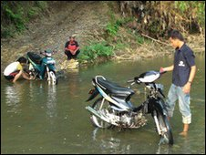 Two villagers washing their motorbikes at the river