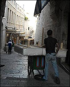 A man transporting a bed on a cart through the Old City's narrow streets