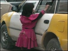 A small child begs at the window of a car