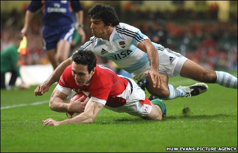 A grinning Stephen Jones dives over for Wales' opening try after fooling Argentina