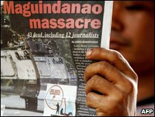 A man reads a daily newspaper that runs a front page story about the massacre